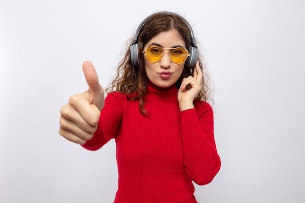 Belle jeune femme en col roulé rouge avec des écouteurs portant des lunettes jaunes heureuse et joyeuse en profitant de sa musique préférée montrant les pouces vers le haut