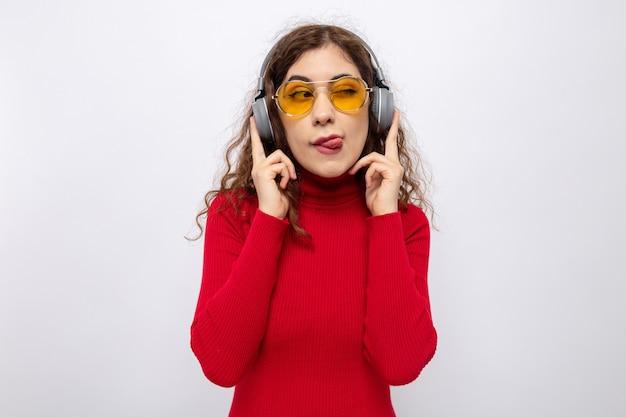 Belle jeune femme à col roulé rouge avec des écouteurs portant des lunettes jaunes heureuse et joyeuse regardant de côté qui sort la langue debout sur un mur blanc