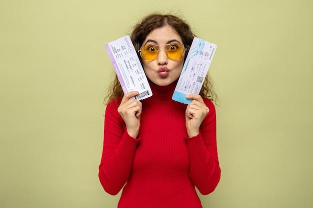 Belle jeune femme en col roulé rouge portant des lunettes jaunes tenant des billets d'avion heureux et positif debout sur le vert