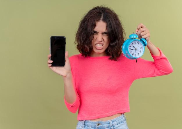 Belle jeune femme en colère tenant un téléphone mobile et un réveil sur un mur vert isolé
