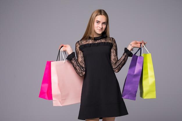 Belle jeune femme commerçante avec quatre sacs en mains
