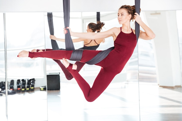Belle jeune femme concentrée pratiquant différentes positions de yoga antigravité sur le miroir