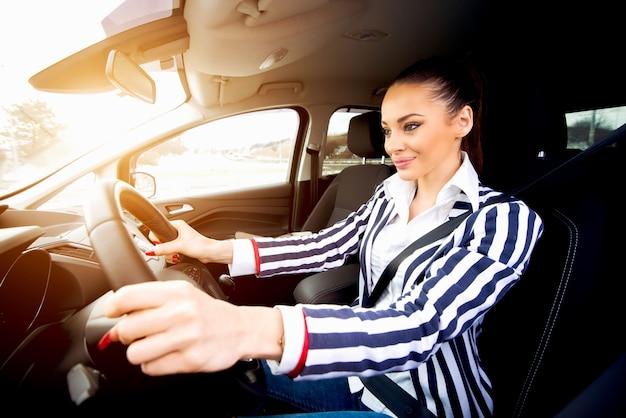 Belle jeune femme conduisant une voiture en souriant et en se concentrant sur la balade.