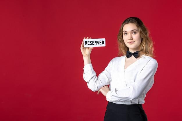 Belle jeune femme confiante serveur papillon sur le cou et tenant une icône réservée sur fond rouge