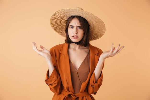 Belle jeune femme confuse portant un chapeau de paille et une tenue d'été isolée sur un mur beige