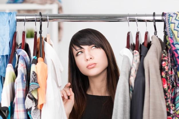 Belle jeune femme confuse près de rack avec des vêtements