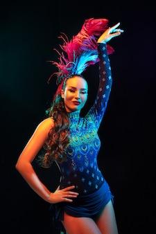 Belle jeune femme en costume de carnaval et de mascarade en néons colorés sur fond noir