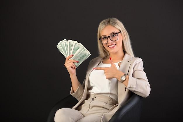 Belle jeune femme en costume noir avec des dollars en mains