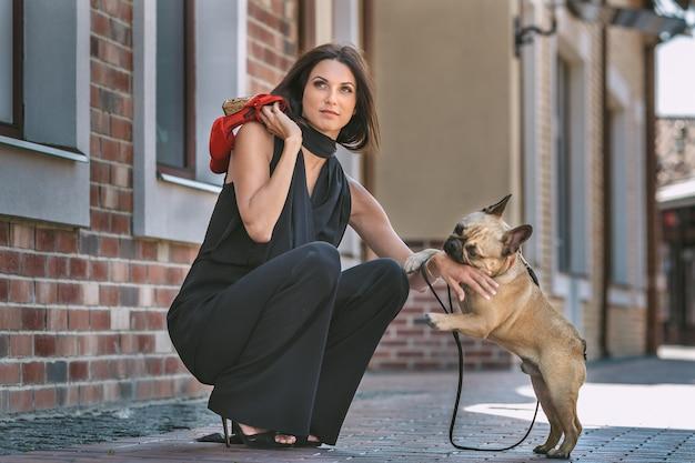Belle jeune femme en costume noir avec mignon petit chien chiot posant dans la rue