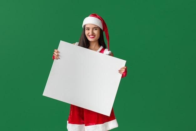 Belle jeune femme en costume de père noël et avec une affiche vierge sur une surface de couleur