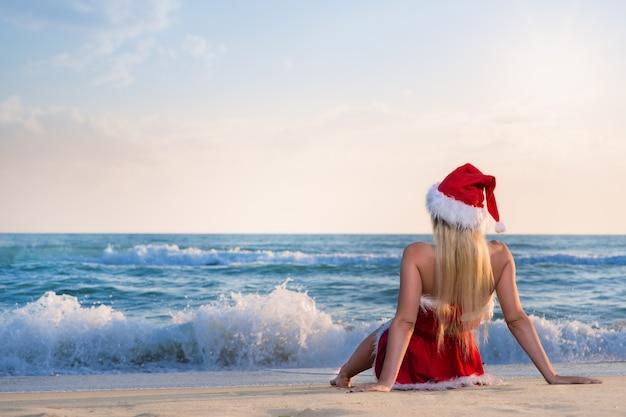 Belle jeune femme en costume de père noël célèbre noël lors d'un voyage dans des pays chauds sur la plage de sable de la mer