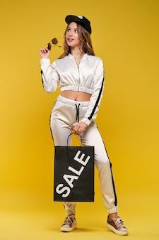 Belle jeune femme en costume de sport avec un sac à provisions sur un mur jaune