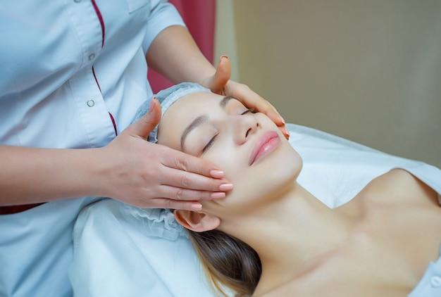 Belle jeune femme couchée avec les yeux fermés et massage du visage et de la tête au spa