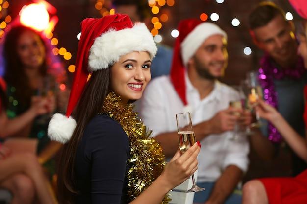 Belle jeune femme avec une coupe de champagne à la fête de noël