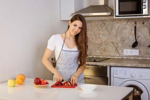 Belle jeune femme coupe les pommes rouges avec un couteau dans la cuisine le concept de régime et une alimentation saine