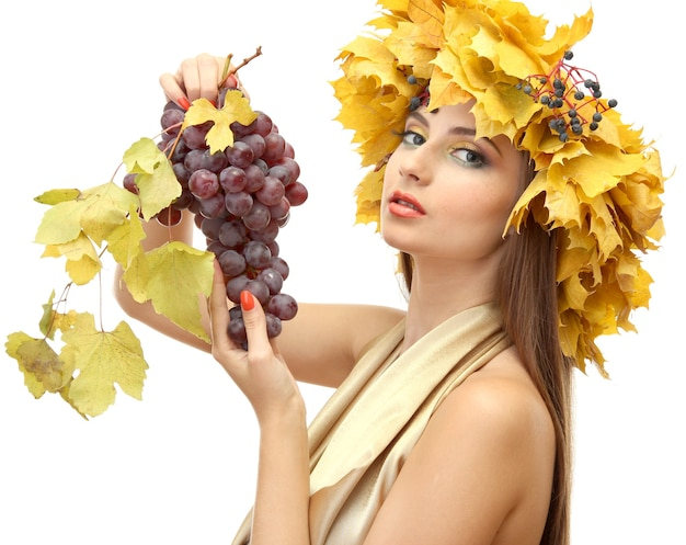 Belle jeune femme avec une couronne d'automne jaune et des raisins, isolé sur blanc