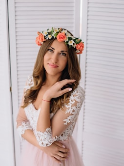 Belle jeune femme avec une couronne de printemps sur sa tête et en peignoir rose posant en studio blanc