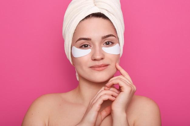 Belle jeune femme avec des coussinets de collagène sous les yeux, porte une serviette blanche sur la tête