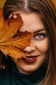 Belle jeune femme couvrant le visage avec des feuilles