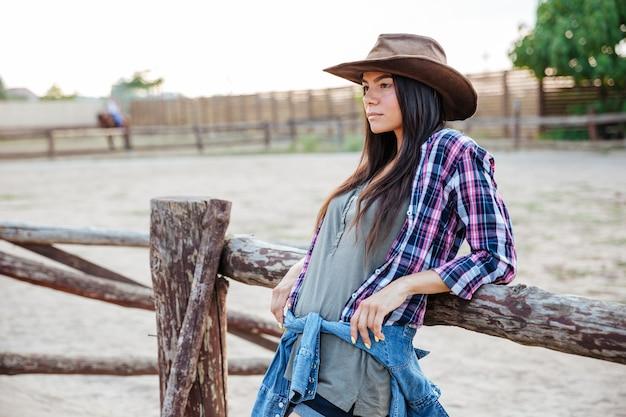 Belle jeune femme cow-girl en chapeau et chemise à carreaux debout et se détendre à l'extérieur