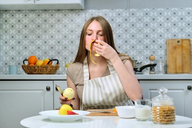 Belle jeune femme cuisine de délicieux aliments diététiques sains à la maison. sur la table sont des fruits, des céréales, des produits laitiers. beauté, jeunesse, mode de vie sain et alimentation saine