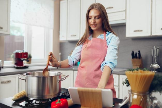 Belle jeune femme cuisiner quelque chose près de la cuisinière dans sa cuisine