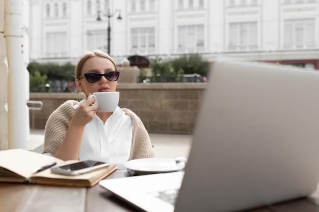 Belle jeune femme dans un café de la rue boit du café