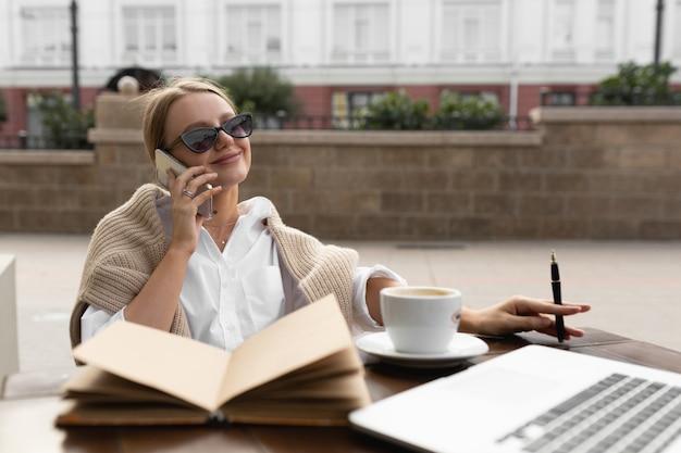 Belle jeune femme dans un café de la rue, parler au téléphone