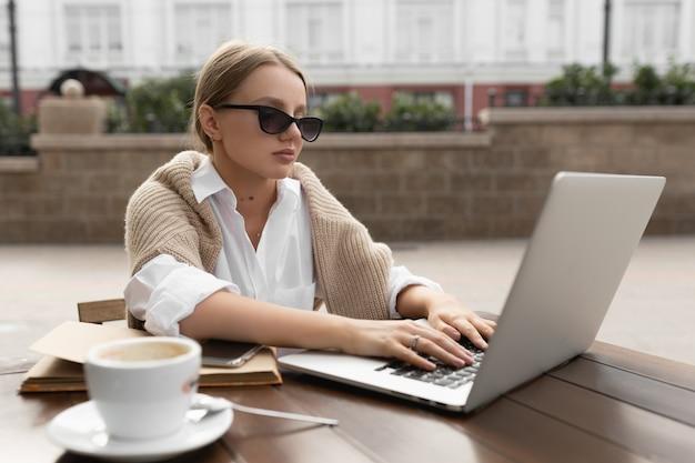 Belle jeune femme dans un café de la rue tape du texte sur l'ordinateur
