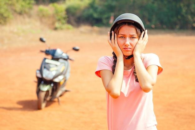 Belle et jeune femme dans un casque de sécurité se tient près de la moto (vélo) et crie de peur. le concept de conduite sûre d'un scooter et d'un accident
