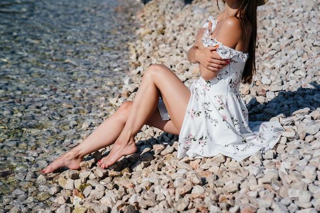 Une belle jeune femme dans un chapeau, des lunettes et une robe légère est assise dos à l'océan sur fond d'énormes rochers par une journée ensoleillée. tourisme et voyages touristiques.