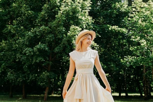 Belle jeune femme dans un chapeau de paille et une robe blanche dans un parc verdoyant ou une forêt un jour d'été