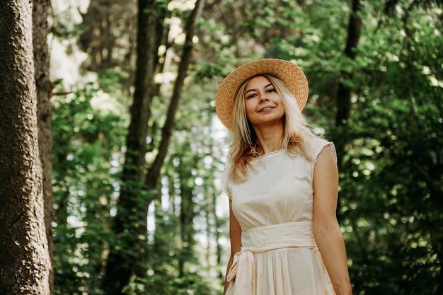Belle jeune femme dans un chapeau de paille et une robe blanche dans un parc verdoyant