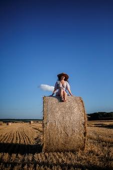 Une Belle Jeune Femme Dans Un Chapeau Et Une Robe D'été Est Assise Sur Une Gerbe De Foin Dans Un Champ. Nature Rurale, Champ De Blé Photo Premium