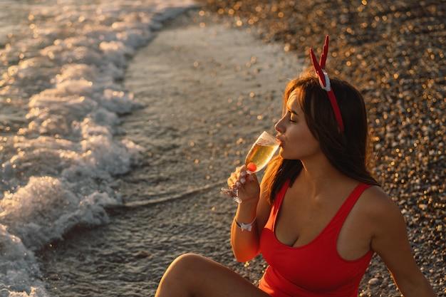 Belle jeune femme dans un chapeau de santa avec un verre de champagne dans ses mains marche sur la plage