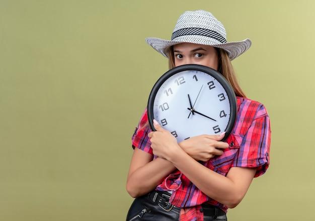 Une belle jeune femme dans une chemise à carreaux tenant une horloge murale