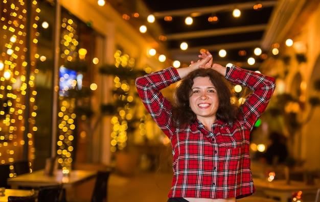 Belle jeune femme dans une chemise rouge sur fond d'une ville de nuit