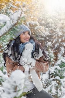 Belle jeune femme dans les chutes de neige dans la forêt en hiver
