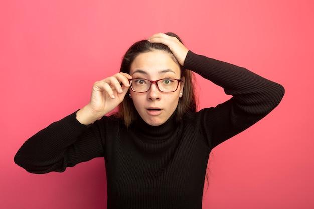 Belle jeune femme dans un col roulé noir et des lunettes à l'avant d'être confus en touchant ses lunettes debout sur un mur rose