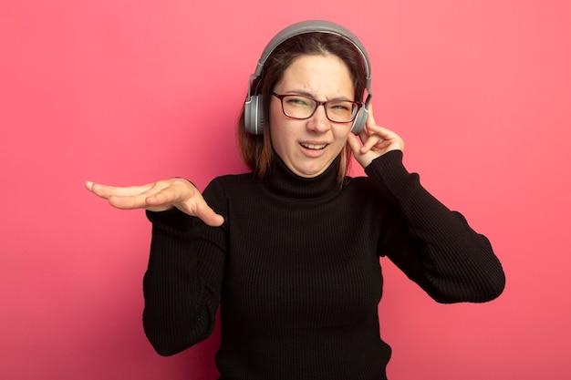 Belle jeune femme dans un col roulé noir et des lunettes avec des écouteurs appréciant sa musique préférée debout sur le mur rose