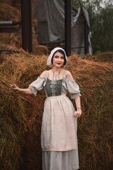 Belle jeune femme dans un costume traditionnel bavarois est debout près des meules de foin à la ferme