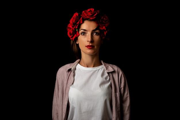 Belle jeune femme dans une couronne de fleurs rouges