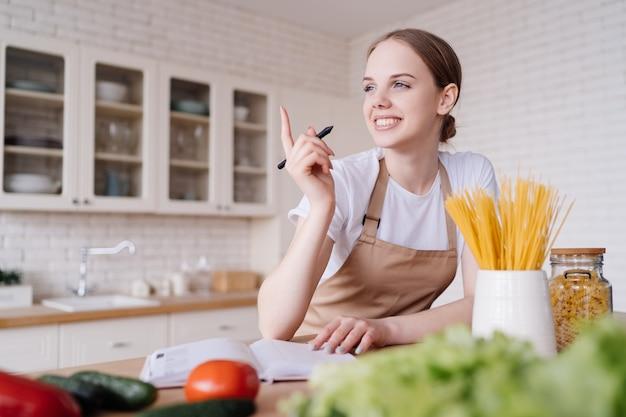Belle jeune femme dans la cuisine dans un tablier écrit ses recettes préférées à côté de légumes frais
