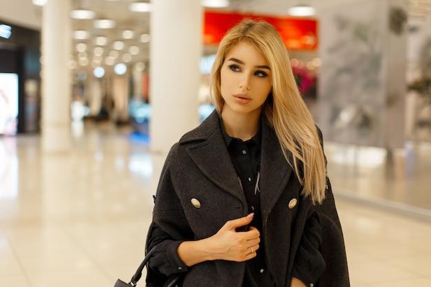 Belle jeune femme dans un élégant manteau à la mode shopping au centre commercial
