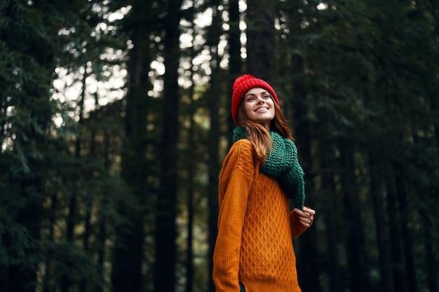 Belle jeune femme dans la forêt dans des vêtements lumineux, un chapeau rouge, un pull orange, dans une écharpe verte voyage, randonnée dans la nature dans la forêt