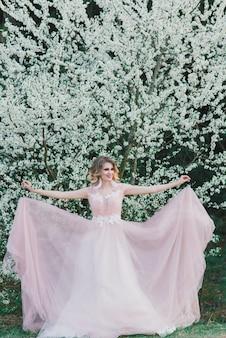 Belle jeune femme dans le jardin fleuri. mariée en robe de mariée
