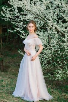 Belle jeune femme dans le jardin fleuri. la mariée.