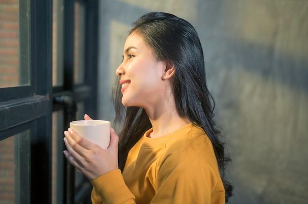 Une belle jeune femme dans la lumière du soleil appréciant son café du matin à la maison