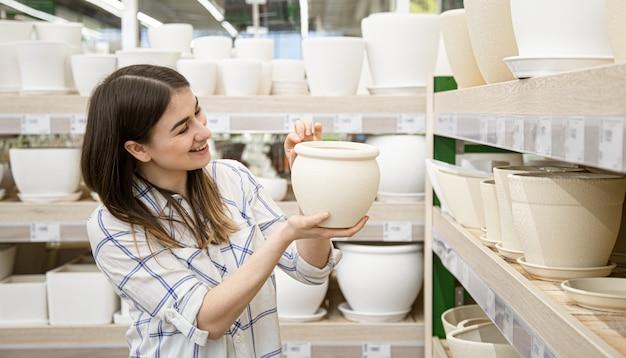 Belle jeune femme dans un magasin de fleurs choisit un pot de fleurs.
