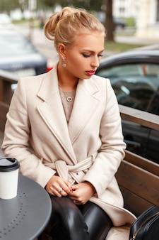 Belle jeune femme dans un manteau d'automne beige classique se trouve dans un café